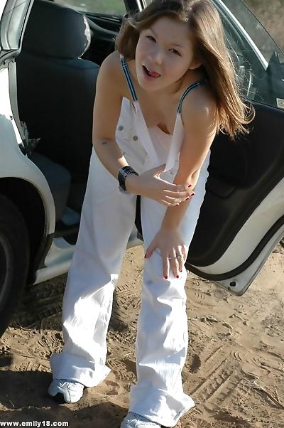 Emily posing in her car in..